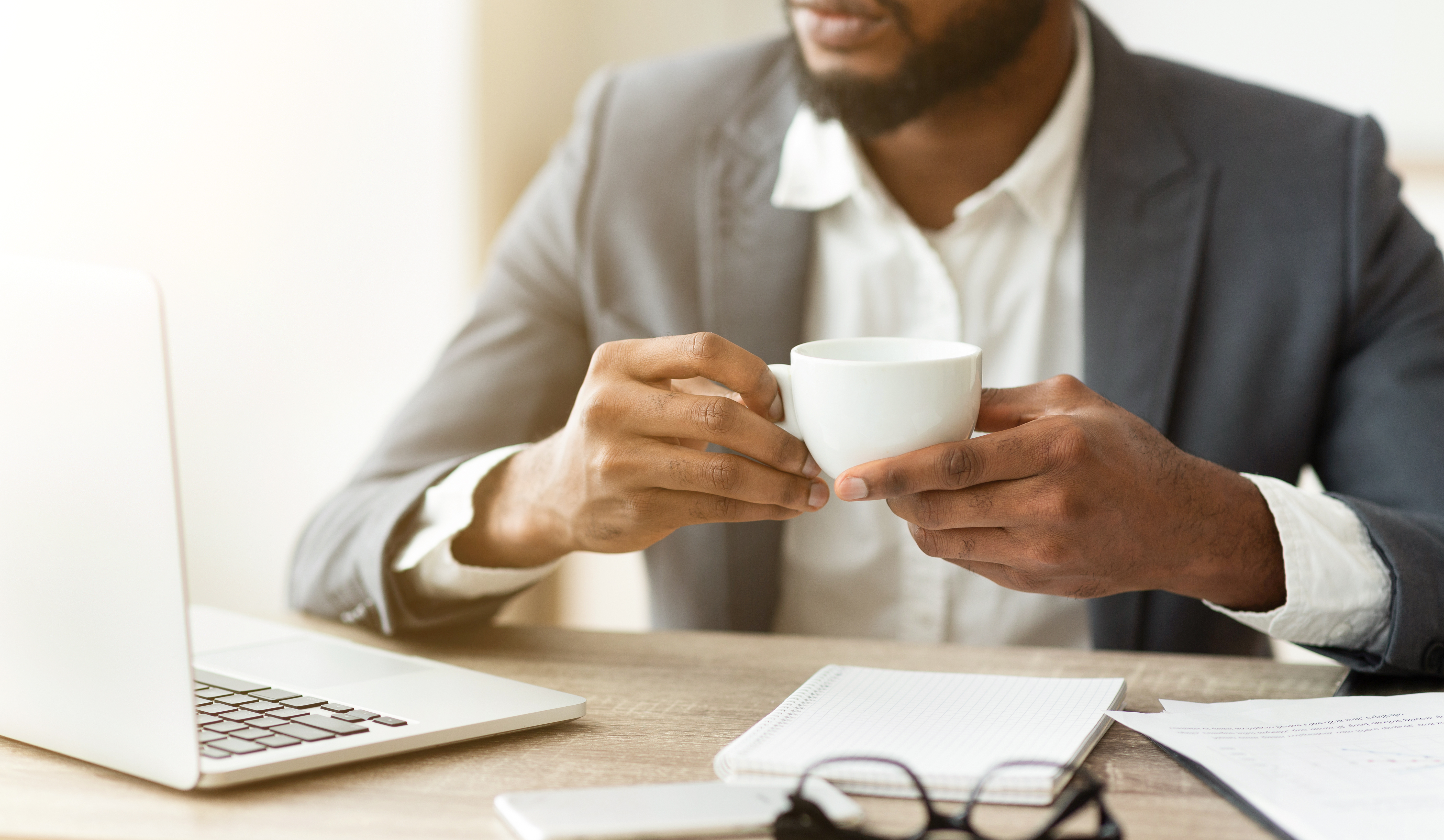 businessman drinking coffee at workplace, thinking about new project.